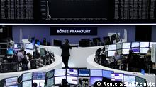 Traders work at their desks in front of the German share price index, DAX board, at the stock exchange in Frankfurt, Germany, January 7, 2016. European shares fell sharply on Thursday after China accelerated the depreciation of the yuan, sending currencies across the region reeling and domestic stock markets tumbling. REUTERS/Staff/Remote