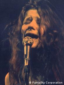 Mit schmerzverzertem Gesicht singt Janis Joplin ins Mikrofon
