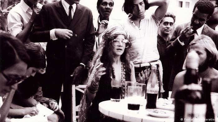 Scene from the film JANIS: LITTLE GIRL BLUE, with Janis Joplin surrounded by friends at a party (Fantality Corporation)