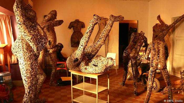 Freddy Tsimba in his living room surrounded by metal sculptures