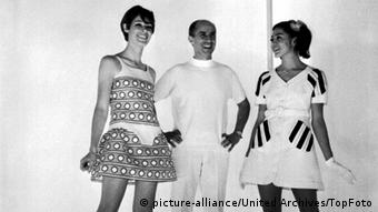 Courreges is flanked by two models waering his mini length dresses from his 1968 spring and summer collections