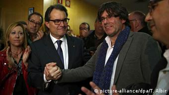 Catalonian acting President Artur Mas (L) shakes hands with Gerona's Mayor Carles Puigdemont
