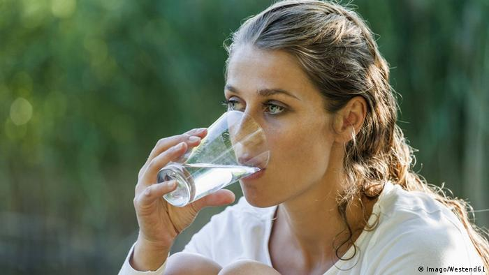 Woman drinking a glass of water (Imago/Westend61)