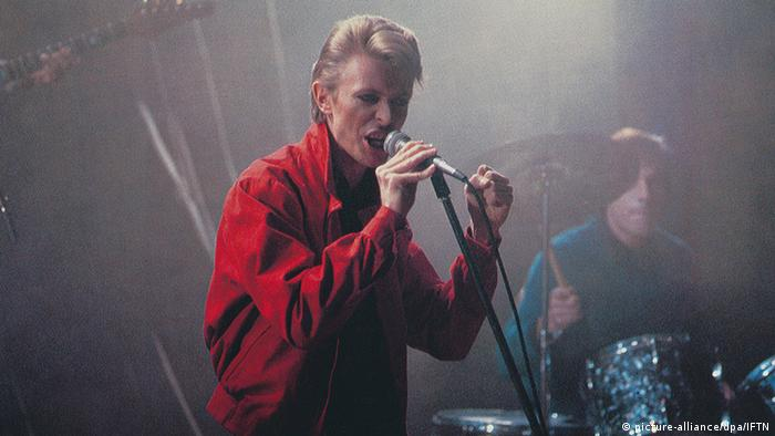 David Bowie steht auf einer Bühne und singt in einer Szene von Wir Kinder vom Bahnhof Zoo von 1981.