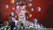 January 11, 2016 A woman leaves a bouquet at a mural of David Bowie in Brixton, south London, January 11, 2016. David Bowie, a music legend who used daringly androgynous displays of sexuality and glittering costumes to frame legendary rock hits Ziggy Stardust and Space Oddity, has died of cancer. REUTERS/Stefan Wermuth (c) Reuters/S. Wermuth
