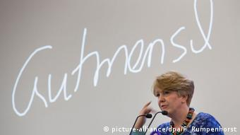 Janich stands before the word gutmensch written on the wall