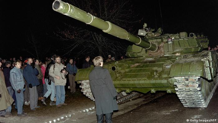 A Lithuanian demonstrator stands in front of a Soviet tank on January 13, 1991, in Vilnius