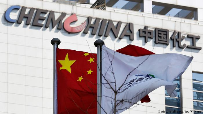 A Chinese national flag and a company flag fly in front the logo of China National Chemical Corporation (ChemChina)