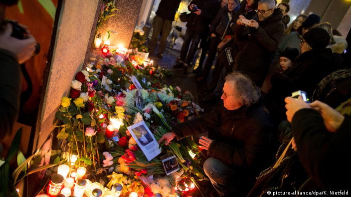 people look at candles and flowers making up a memorial