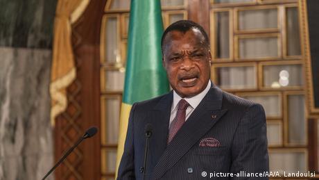 Denis Sassou Nguesso, im Hintergrund eine grün-gelbe Flagge