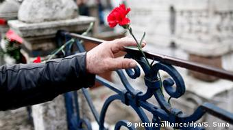 A mourner places a red rose in the railing at the Blue Mosque in Istanbul to remember the victims of Tuesday's attack.