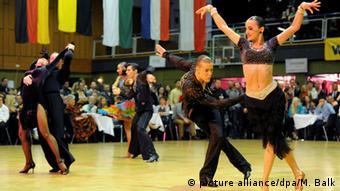 Ausschnitt aus einem Tanzturnier mit drei Paaren, die in schwarzen Kostümen tanzen, die Männer in Hose und Hemd, die Frauen in Kleidern