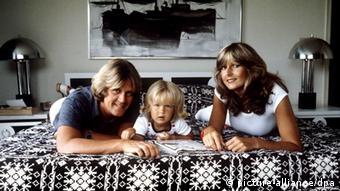 Howard Carpendale liegt mit Sohn und Ehefrau auf einem Bett (Foto: picture-alliance/dpa)
