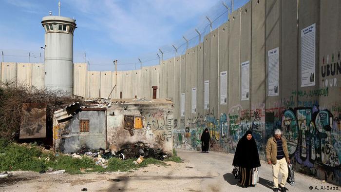 Палестинцы на Западном берегу реки Иордан идут вдоль бетонного заграждения