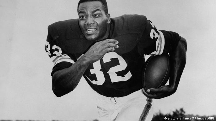Jim Brown in football gear running with the ball