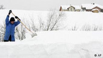 Ein Mann schiebt Schnee vom Dach einer Halle. Quelle: ap