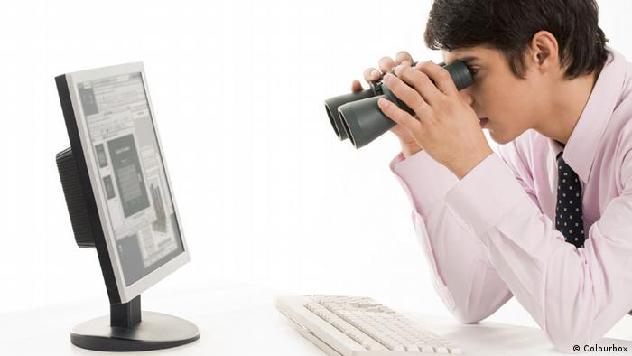 Homem de camisa branca e gravata olha através de um binóculo para a tela do computador