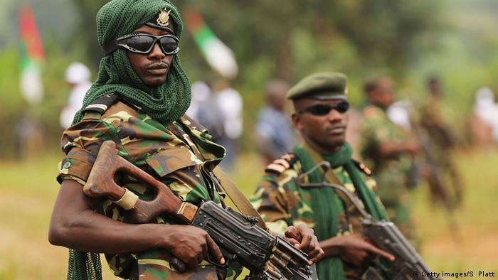 Two armed Burundian soldiers wearing sunglasses, one of them with a headscarf, look into the camera.