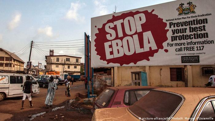 A billboard on a busy street reads 'Stop Ebola'