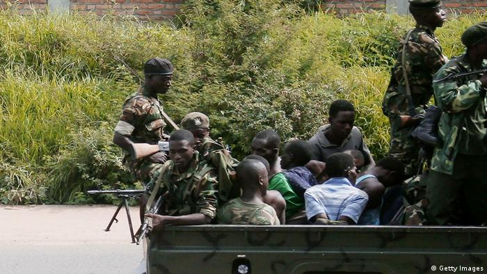 Burundian soldiers in a military vehicle, carrying men tied up