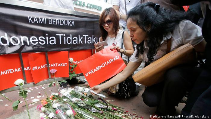 People laying wreaths at the Starbucks in Jakarta (picture-alliance/AP Photo/D. Alangkara)