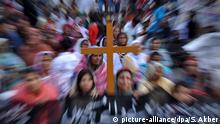 A cross in front of blurred people (picture-alliance/dpa/S. Akber)