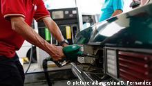 ARCHIV - Ein Mann betankt am 04.04.2012 an einer Zapfsäule in Caracas, Venezuela, ein Auto. Wer in Venezuela mit seinem Auto an die Zapfsäule fährt, verlässt die Tankstelle wohl meist mit einem breiten Grinsen. Das Land hat die billigsten Spritpreise der Welt. Möglich macht's der Staat. EPA/David Fernández dpa (zu dpa Sprit zum Spottpreis: In Venezuela ist Benzin billiger als Wasser vom 28.09.2012) +++(c) dpa - Bildfunk+++ Copyright: picture-alliance/dpa/D. Fernandez