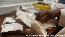 In this photo taken Tuesday Oct. 20, 2015, a money changer counts Nigerian naira currency at a bureau de change, where a dollar buys 222 naira compared to the official rate of 198, in Lagos, Nigeria. The IMF is pressing Nigeria to further devalue its naira currency amid uncertainty over the political and economic outlook for Africa's biggest oil producer and economy. Analysts said there's disappointment that President Muhammadu Buhari's long-awaited Cabinet list includes no economic stars. The naira has lost 25 percent of its value in the past year and the stock market has plummeted because of political uncertainty and halved prices for oil that provides most government revenue.(AP Photo/Sunday Alamba) Copyright: picture-alliance/AP Photo/S. Alamba