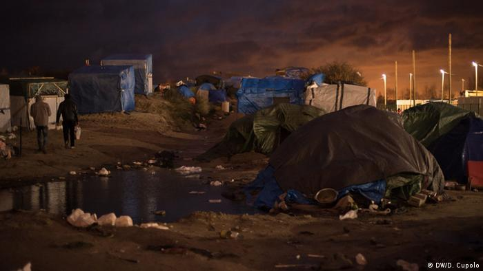 Tents at dusk next to rubbish and a large puddle