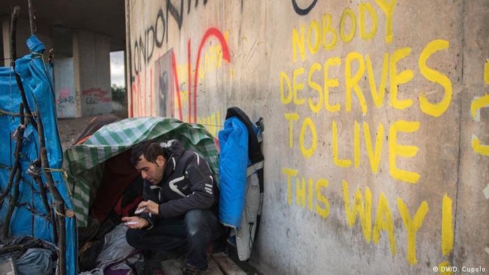Ein Bewohner des Lagers drückt sich an eine Mauer