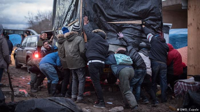 Volunteers help migrants move a shelter on a truck