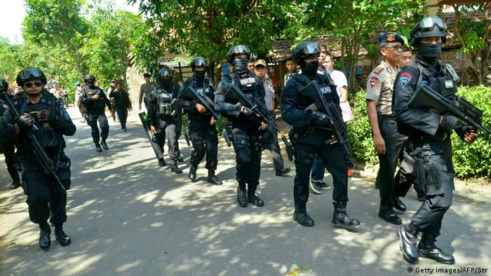 Indonesian police dressed in riot gear walk down a street.