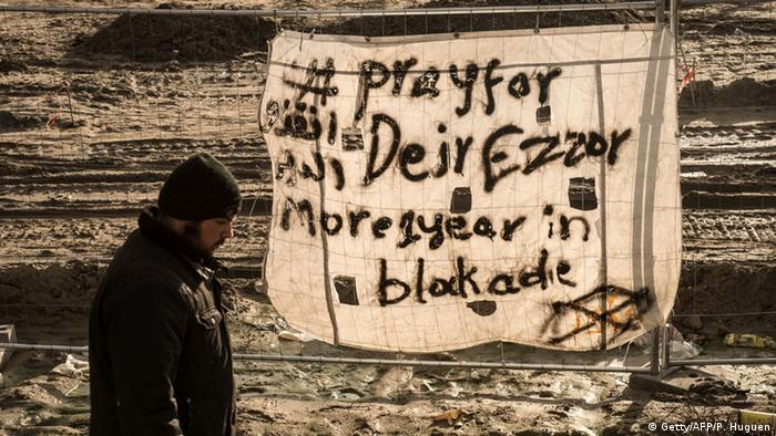 Black paint on a large canvas says, pray for Deir Ezzor, using an alternative spelling for Deir al-Zor.