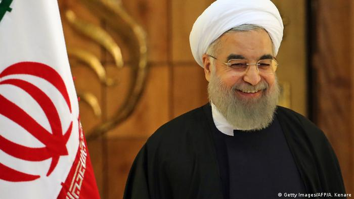Rouhani stands in front of an Iranian flag
