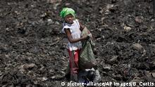 In this photo taken Thursday, Nov. 12, 2015, Joyce Njeri, 8, walks with a torn sack carrying the plastic bottles she has scavenged, at the garbage dump in the Dandora slum of Nairobi, Kenya. Men, women and children traipse through the murky sludge that weaves through mountains of garbage in Nairobi's notorious Dandora dump, hunting for anything that can be recycled to earn themselves enough for their daily bread - some of the poorest of Kenya's poor and those likely to be on Pope Francis' mind when he makes his first trip to Africa this week and brings his message of environmental stewardship and care for society's most marginal. (picture-alliance/AP Images/B. Curtis)