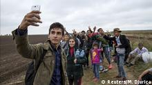 05.09.2015 ***** Alvand, 18, from Kobani, Syria takes a selfie with his friends as they walk along a railway track after crossing into Hungary from the border with Serbia near the village of Roszke September 5, 2015. Austria and Germany threw open their borders to thousands of exhausted migrants on Saturday, bussed to the Hungarian border by a right-wing government that had tried to stop them but was overwhelmed by the sheer numbers reaching Europe's frontiers. REUTERS/Marko Djurica TPX IMAGES OF THE DAY @ Reuters/M. Djurica