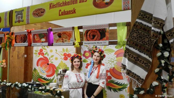 Олександра (праворуч) знайомить відвідувачів виставкою з кухнею Луганщини