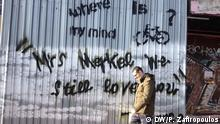Pedestrians walk by a graffiti outside a building site at a major intersection in central Athens. Stichwort: Griechenland-Krise und der Alltag Copyright: Pavlos Zafiropoulos, DW, Athens, Jan 2016