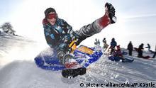 Kinder Rodeln Schlitten fahren Schneeschanze