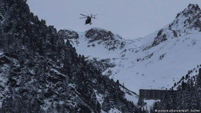 An helicopter flies to the site of an avalanche near Valfrejus, France