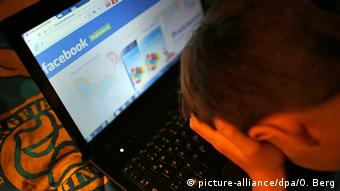 Boy holds his head in front of a laptop screen showing a Facebook page.
