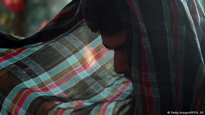 A Pakistan child abuse victim conceals his face during an interview in 2015