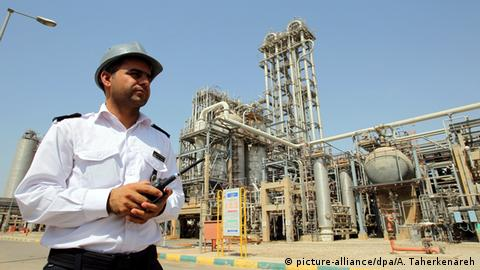 An Iranian oil worker in front of a refinery