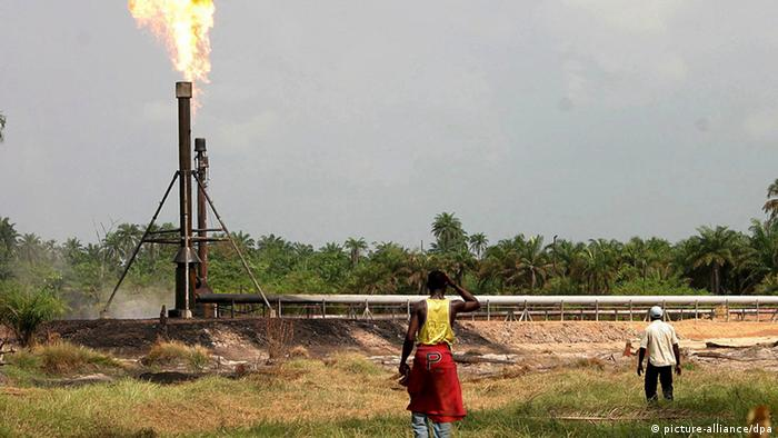 Oil company worker moving toward a gas flare in Niger Delta