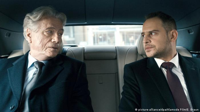 Jürgen Prochnow and Moritz Bleibtreu wearing suits and sitting in a car.