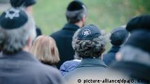 Teilnehmer mit einer jüdischen Kopfbedeckung für Männer, der Kippa, stehen am 09.11.2015 während einer Kranzniederlegung vor der Semper-Synagoge in Dresden. Die Stadt gedachte der Opfer der Reichspogromnacht vor 77 Jahren. Foto: Oliver Killig/dpa +++(c) dpa - Bildfunk+++ +++ (C) picture-alliance/dpa/O. Killig