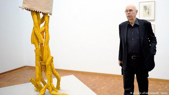 Claes Oldenburg beside a sculpture