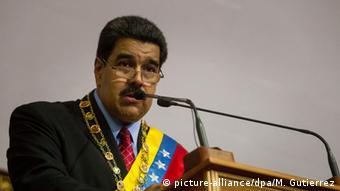 Venezuelan President Nicolas Maduro, wearing a sash, delivers a speech