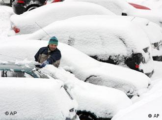 A man clears snow from the roof of his car