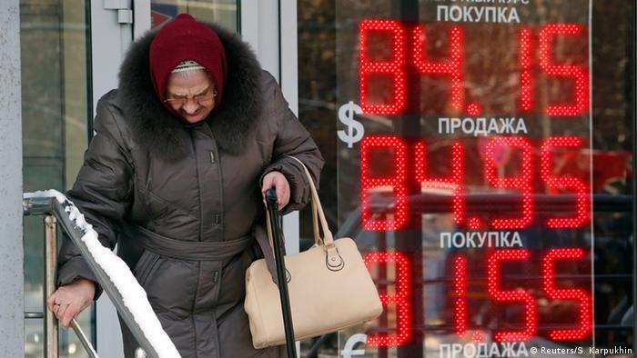 Москва: възрастна жена минава покрай табло с обменните курсове на основните валути